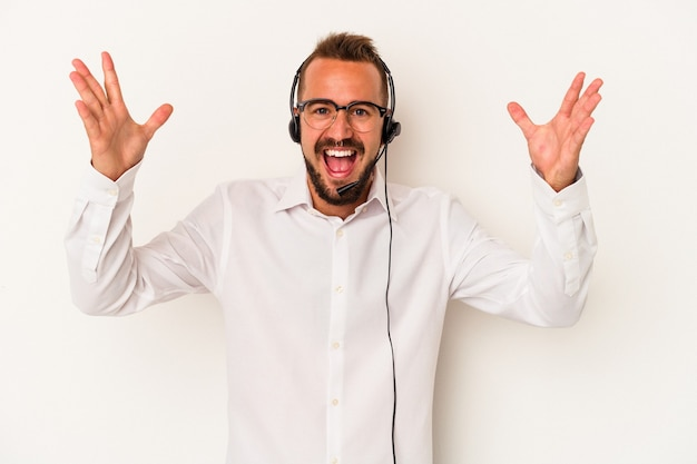 白い背景に分離された入れ墨を持つ若い白人のテレマーケターの男は、嬉しい驚きを受け取り、興奮し、手を上げます。 Premium写真