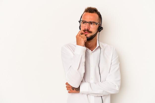 白い背景で隔離の入れ墨を持つ若い白人のテレマーケターの男は、コピースペースを見ている何かについて考えてリラックスしました。