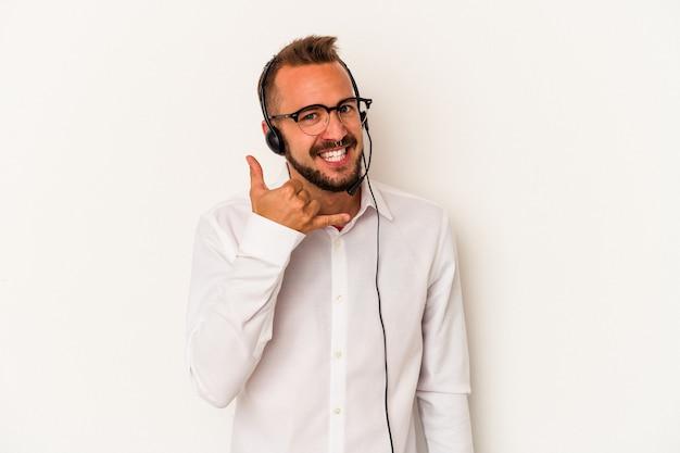 指で携帯電話の呼び出しジェスチャーを示す白い背景で隔離の入れ墨を持つ若い白人テレマーケティングの男。