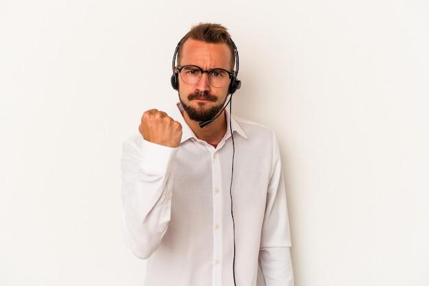 カメラに拳、攻撃的な表情を示す白い背景に分離された入れ墨を持つ若い白人のテレマーケターの男。
