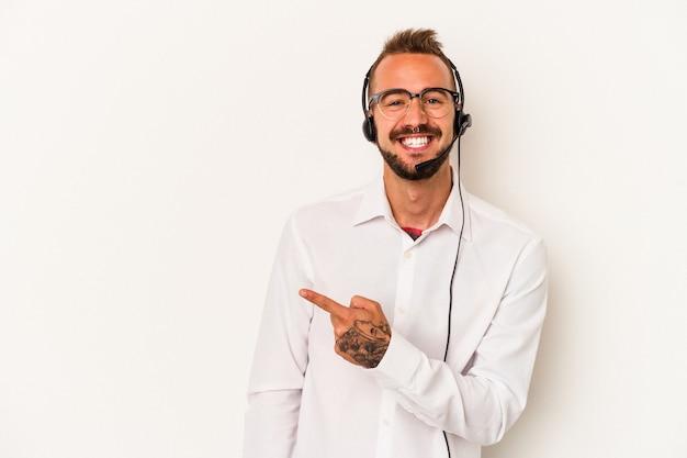 空白のスペースで何かを見せて、笑顔で脇を指して、白い背景で隔離の入れ墨を持つ若い白人のテレマーケターの男。