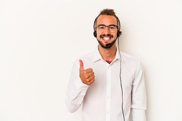 笑顔と親指を上げて白い背景で隔離の入れ墨を持つ若い白人テレマーケター男