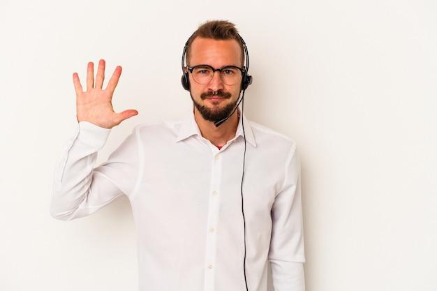 白い背景に分離された入れ墨を持つ若い白人のテレマーケターの男は、指で5番を示して陽気に笑っています。