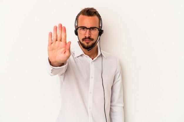 白い背景に隔離された入れ墨を持つ若い白人のテレマーケターの男は、一時停止の標識を示している手を伸ばして立って、あなたを防ぎます。