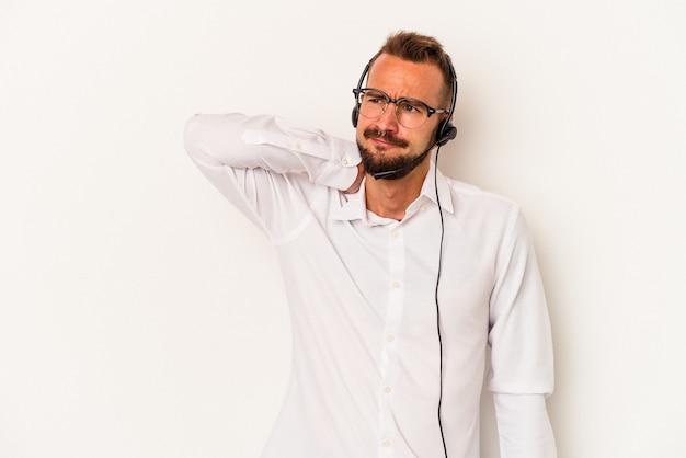 頭の後ろに触れて、考えて、選択をする白い背景に分離された入れ墨を持つ若い白人のテレマーケターの男。