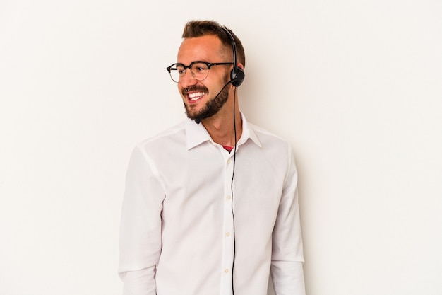 Young caucasian telemarketer man with tattoos isolated on white background  looks aside smiling, cheerful and pleasant.