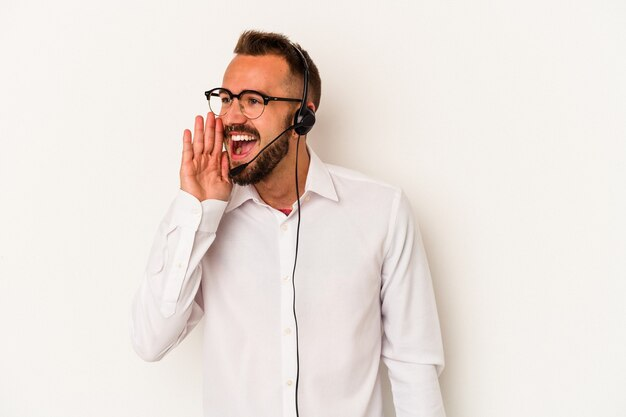 Young caucasian telemarketer man with tattoos isolated on white background  shouting and holding palm near opened mouth.