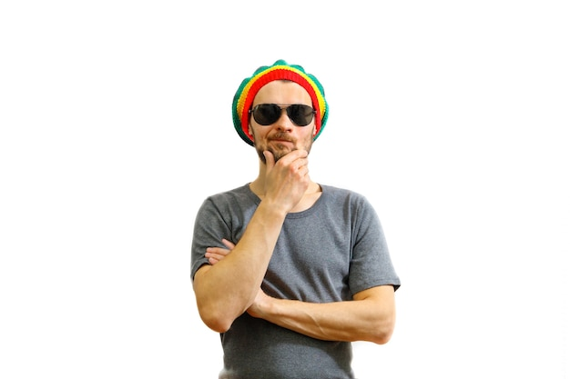 Young caucasian think man in rasta hat, sunglasses and grey t-shirt on white background.