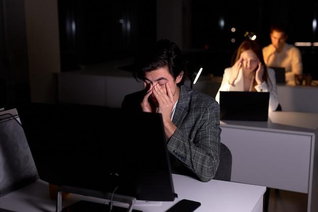 양복을 입은 젊은 백인 브루네트 남자는 밤에 사무실에 앉아 있고, 눈은 과로로 다치고, 두통으로 고통받고 있습니다. 남자 회사원은 기한을 지키지 않습니다. 복사 공간