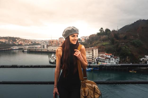 Pasaia의 높은 관점에서 만을 바라보는 백인 젊은 관광 여성; 바스크 국가.