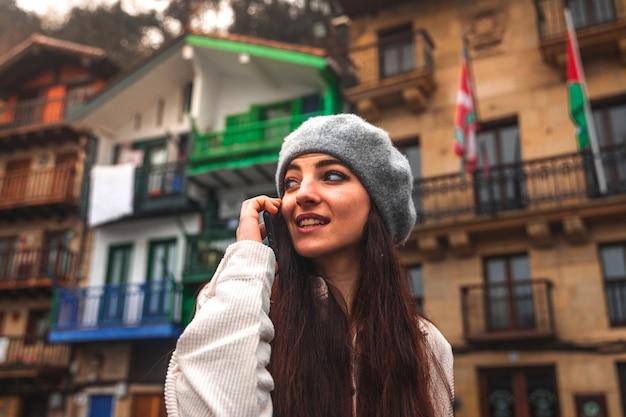 구시가지에서 스마트폰을 사용하는 젊은 백인 관광 여성.