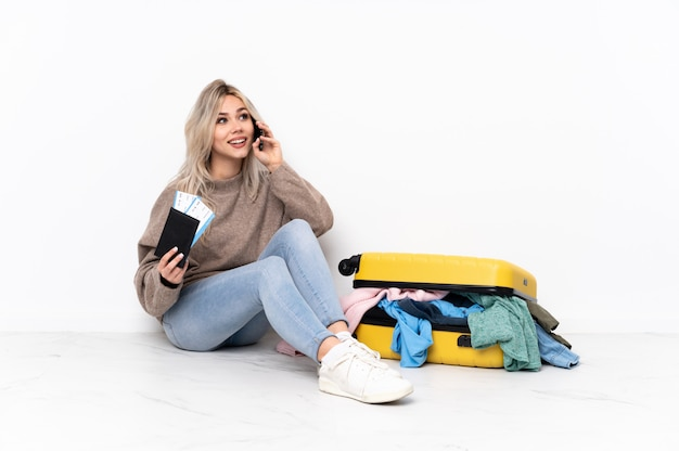 Young caucasian travel woman over sitting on the floor