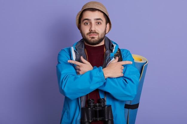 青い背景に分離された若い白人旅行者バックパッカー男、両側を指して、どこに行くかわからない、ジャケットを着て