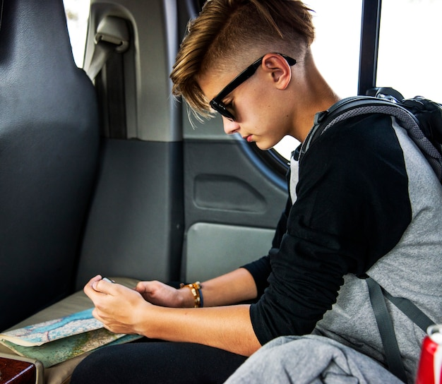 Young caucasian traveler boy sitting in a van using mobile phone