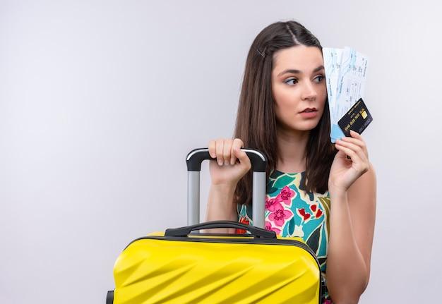 Молодой кавказский путешественник девушка держит билеты на самолет и чемодан на изолированном белом фоне