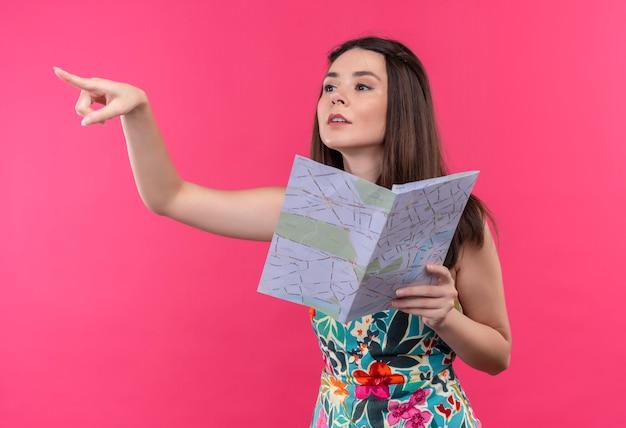 Молодой кавказский путешественник девушка держит карту на изолированном розовом фоне