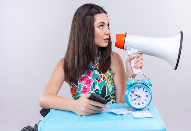 分離の白い背景の上のスピーカーと目覚まし時計、チケット、スーツケースと携帯電話を保持している若い白人旅行者の女の子