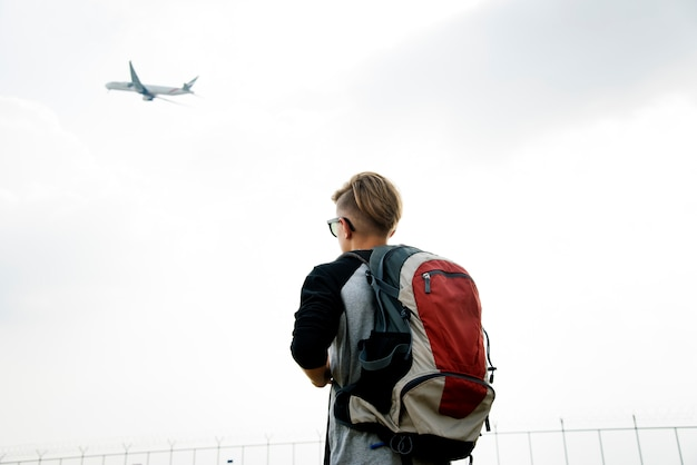 Young caucasian traveler standing outdoors with a takeoff airplane