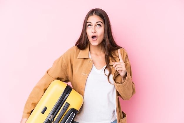 口を開けてスーツケースisolatedpointingを保持している若い白人旅行者女性。