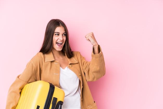 Молодая кавказская путешественница, держащая чемодан, поднимает кулак после победы
