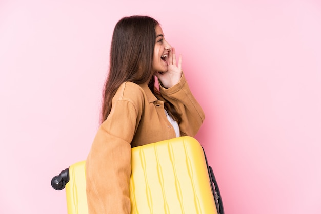 Young caucasian traveler woman holding a suitcase shouting and holding palm near open mouth.