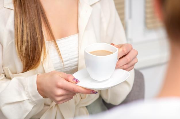 Молодая кавказская до неузнаваемости женщина держит чашку горячего напитка на приеме у врача в больнице