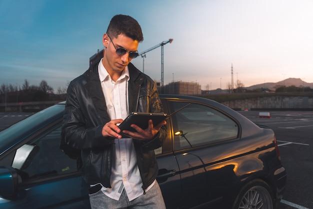 주차장에서 뒤에 스포츠카와 디지털 태블릿을 사용하는 젊은 백인.