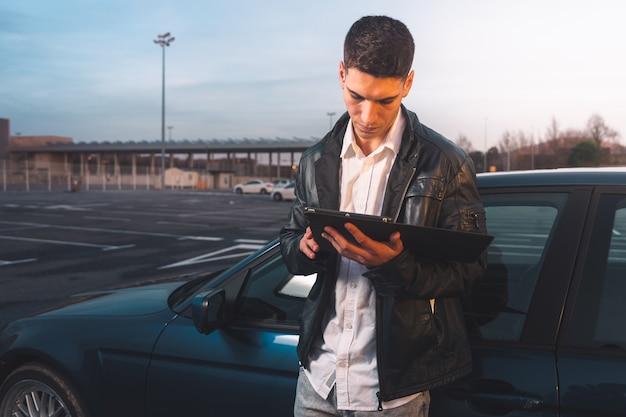 駐車場の後ろにスポーツカーとデジタルタブレットを使用している若い白人。