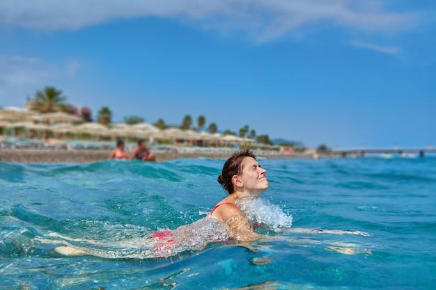 Молодая кавказская белая женщина ныряет в открытую воду во время купания на пляже.