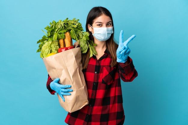 Молодой кавказец с овощами и маской изолирован на синей стене, улыбаясь и показывая знак победы