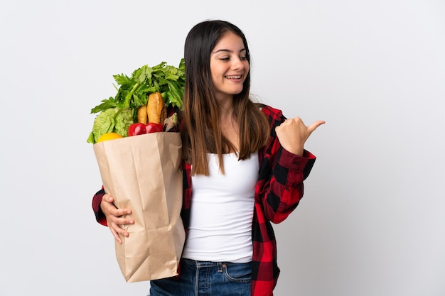 Молодой кавказец с овощами, изолированные на белом фоне, указывая в сторону, чтобы представить продукт