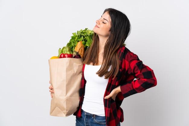 努力したために腰痛に苦しんでいる白い壁に野菜を分離した若い白人
