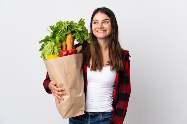 見上げながらアイデアを考えて白い壁に野菜を分離した若い白人