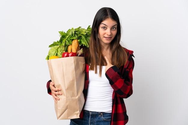 驚きの表情で白い壁に分離された野菜と若い白人