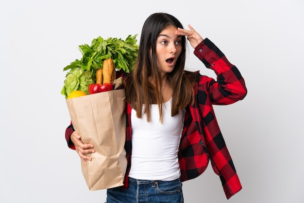 Young caucasian with vegetables isolated on white wall doing surprise gesture while looking to the side