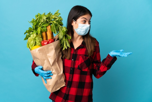 Young caucasian with vegetables and mask isolated on blue wall with surprise facial expression