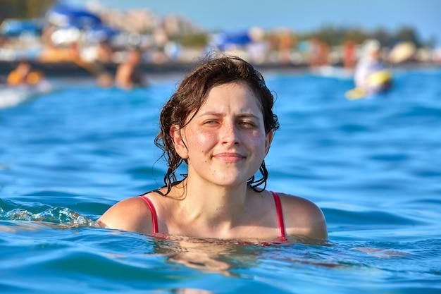 약 19 세의 젊은 백인 여성이 해변에서 휴식을 취할 때 수영을하고 있습니다.