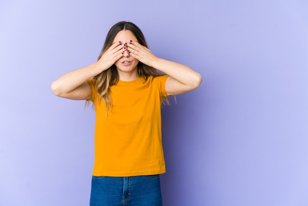 Young caucasian woman afraid covering eyes with hands.