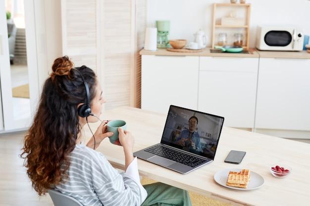 Молодая кавказская женщина и ее азиатский коллега-мужчина работают вместе над проектом, обсуждая его во время видеозвонка
