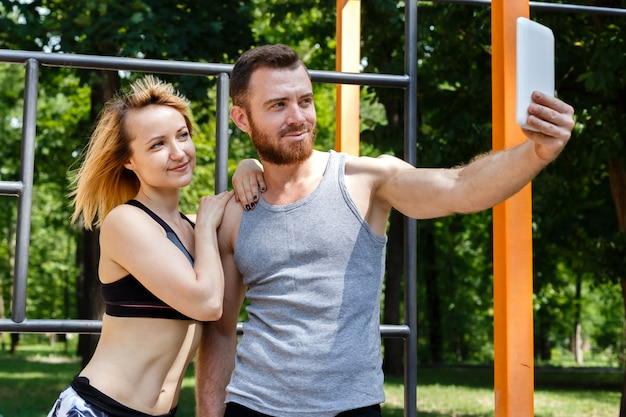Young caucasian woman and a bearded man making selfie photo while doing fitness exercises in park.
