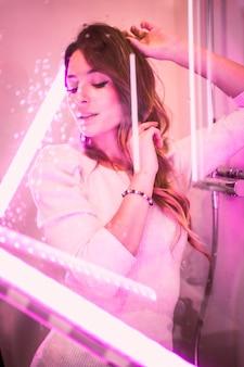분홍색 led 조명, 세로 사진으로 매혹적인 시선으로 카메라를보고 욕조의 젖은 유리 뒤에 젊은 백인 여자