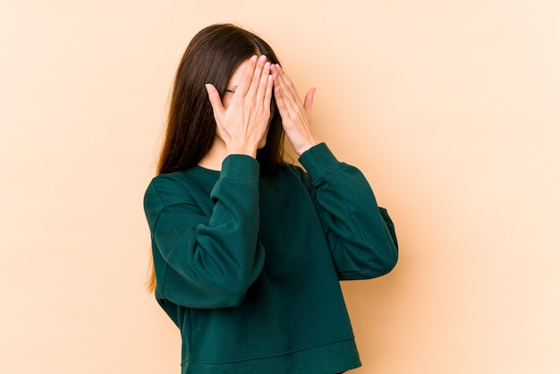 Young caucasian woman on beige wall afraid covering eyes with hands.