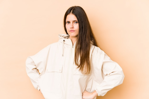 Young caucasian woman on beige wall frowning face in displeasure