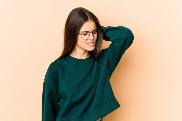 Young caucasian woman on beige wall having a neck pain due to stress, massaging and touching it with hand.