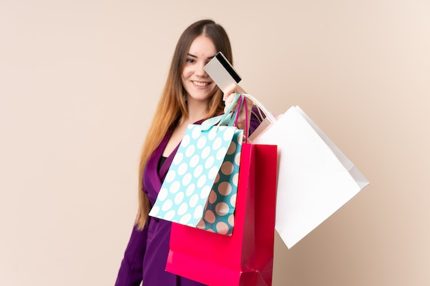 Young caucasian woman on beige wall holding shopping bags and a credit card