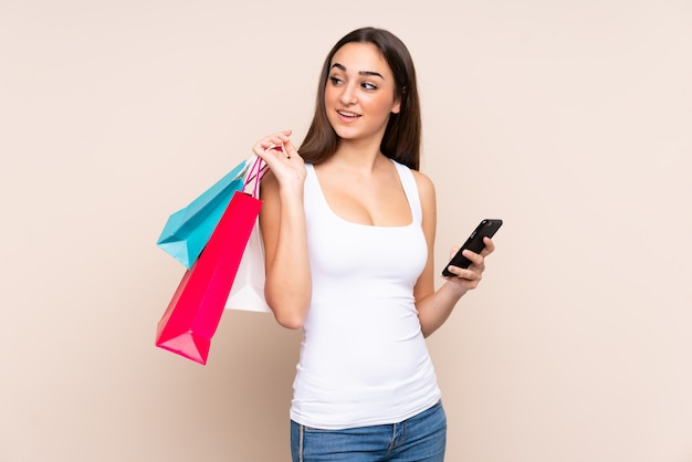 Young caucasian woman on beige wall holding shopping bags and a mobile phone