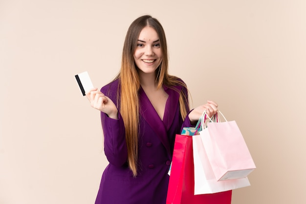 Young caucasian woman on beige wall holding shopping bags and surprised