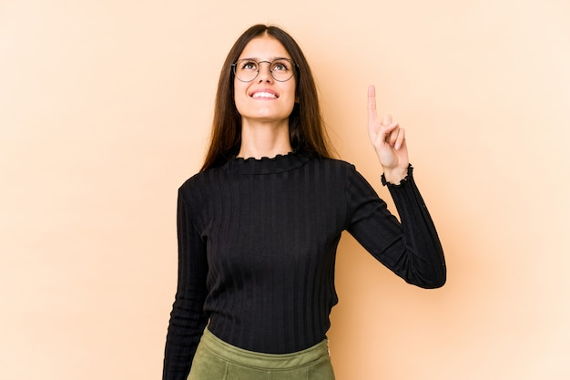 Young caucasian woman on beige wall indicates with both fore fingers up showing a blank space.