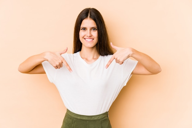 Young caucasian woman on beige wall points down with fingers, positive feeling.