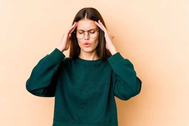 Young caucasian woman on beige wall touching temples and having headache.